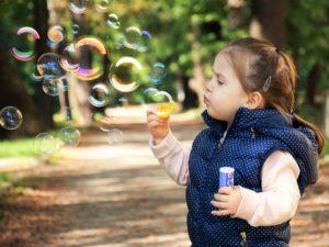 kleines Mädchen macht Seifenblasen